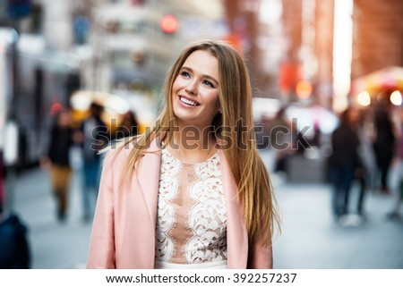 Happy smiling woman looking up and walking on city street  - stock photo