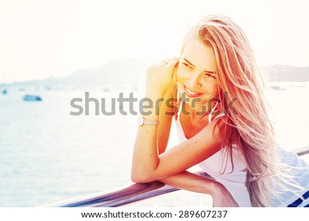 Happy Smiling Woman on a Pier in Sunlights Before Background Blue Sea and Mountains. Summer day - stock photo