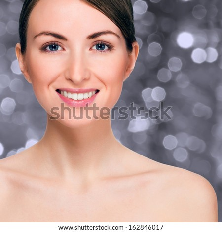 Happy smiling woman over holiday bokeh background with copy-space - stock photo