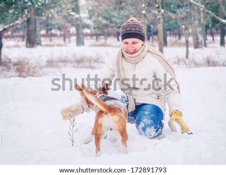 Happy smiling woman  playing with her pet in winter park - stock photo