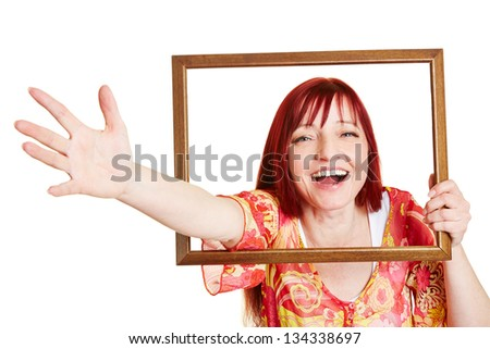Happy smiling woman reaching through empty picture frame - stock photo