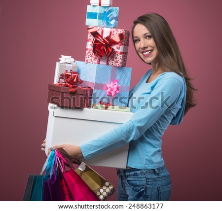 Happy smiling woman shopping and holding a lot of gift boxes - stock photo