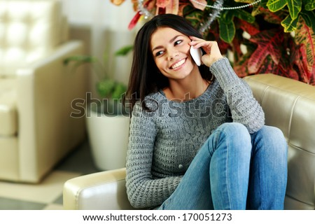 Happy smiling woman talking on the phone at home - stock photo
