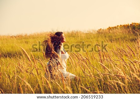 happy smiling woman wearing boho style clothes run through the grass, summer day  - stock photo