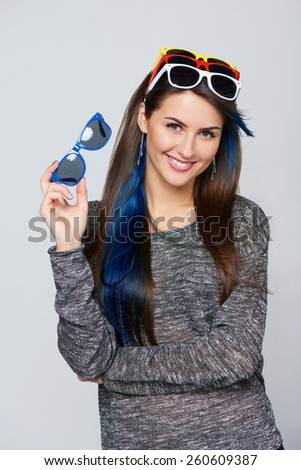 Happy smiling woman wearing many colourful sunglasses on her forehead in the same time, and holding blue one in her hand - stock photo