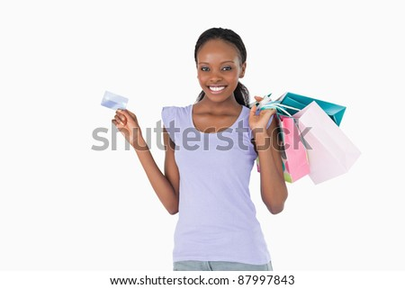 Happy smiling woman with her shopping and credit card on white background - stock photo