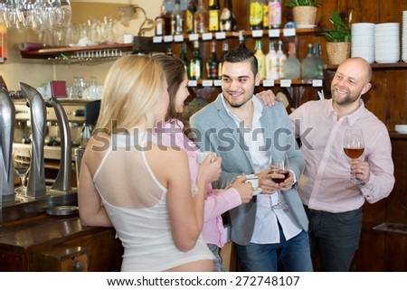 Happy smiling young adults chatting at bar with drinks. Focus on guy