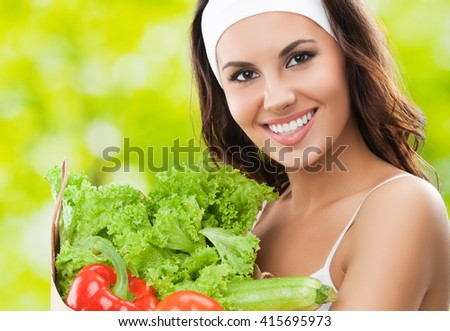 Happy smiling young beautiful brunette woman in fitness wear holding grocery shopping bag with healthy vegetarian raw food, outdoors. Healthy lifestyle, beauty and dieting concept. - stock photo