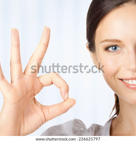 Happy smiling young beautiful business woman showing okay gesture, at office - stock photo