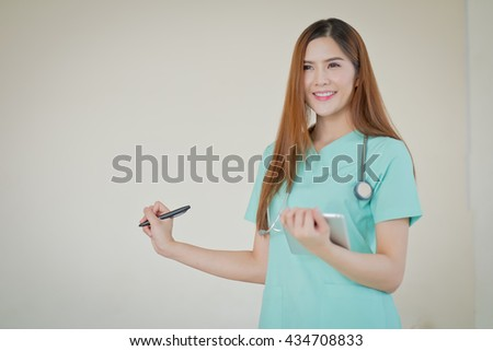 Happy smiling young beautiful female doctor showing blank area for sign or copyspace - stock photo