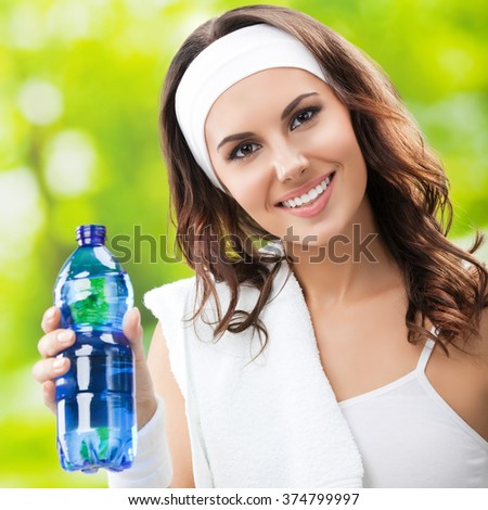 Happy smiling young beautiful woman with bottle of water, outdoors - stock photo