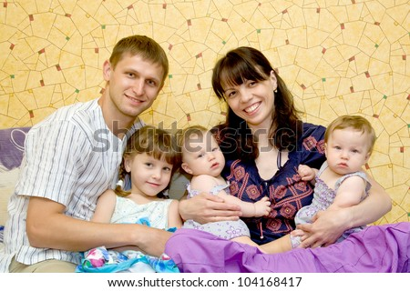 Happy smiling young big family, five people - mother, father, elder daughter and two twins baby girls. The family is sitting at home on the sofa .. - stock photo