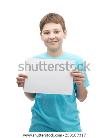 Happy smiling young boy in a cyan t-shirt with a empty copyspace A4 sheet of paper in front of him, composition isolated over the white background - stock photo