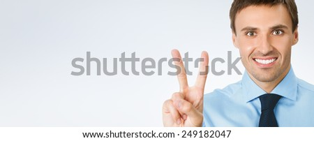 Happy smiling young business man showing two fingers or victory gesture, over grey background, with copyspace area for text or slogan - stock photo