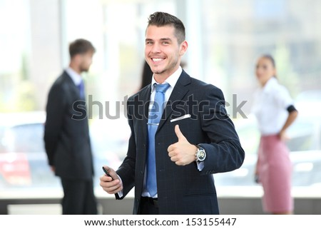 Happy smiling young business man with thumbs up gesture - stock photo