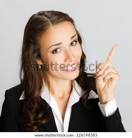 Happy smiling young business woman showing blank area for sign or copyspase, against grey background - stock photo