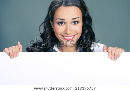 Happy smiling young business woman showing blank signboard, over grey background - stock photo