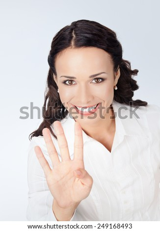 Happy smiling young business woman showing four fingers, against grey background - stock photo