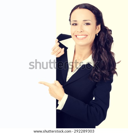 Happy smiling young businesswoman pointing on blank signboard - stock photo