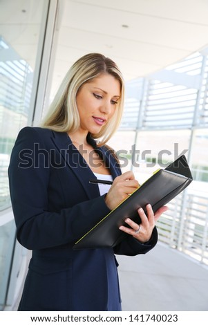 Happy smiling young businesswoman writing in notebook - stock photo