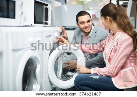 Happy smiling young couple choosing washing machine in hypermarket