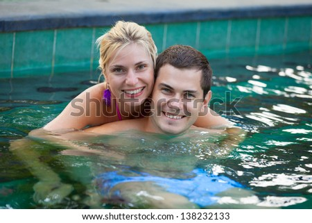 Happy smiling young couple relaxing in a swimming pool in tropical resort - stock photo