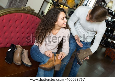 Happy smiling young couple trying on new winter shoes in a shoe store - stock photo