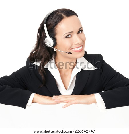 Happy smiling young customer support phone operator in headset showing blank signboard, isolated on white background - stock photo