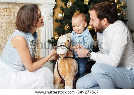 Happy smiling young family near the Christmas tree celebrating New Year. Mom dad and baby sitting on toy horse near the tree. Mother, father and their child on Christmas eve. Mom, dad and child. - stock photo