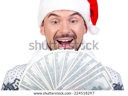 Happy smiling young man in Santa Claus hat with money, isolated on white background - stock photo