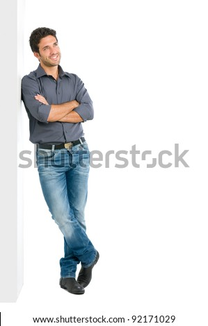 Happy smiling young man leaning against white wall with dreaming and pensive expression, copy space on the right - stock photo