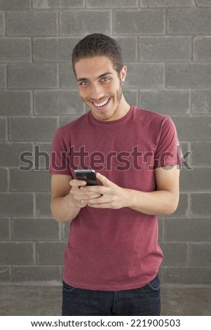 Happy smiling young man portrait touching a mobile screen over brick background, looking at the camera. - stock photo