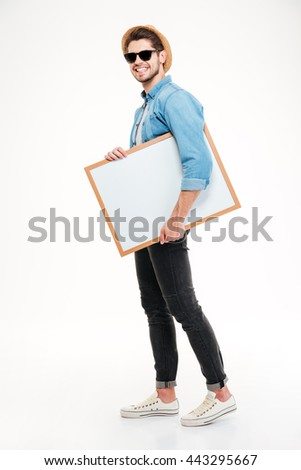 Happy smiling young man walking and holding blank whiteboard over white background - stock photo