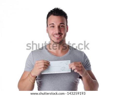 Happy, smiling young man with check (cheque) in hands, looking at camera - stock photo