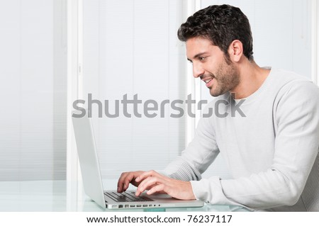 Happy smiling young man working and typing on laptop at home - stock photo
