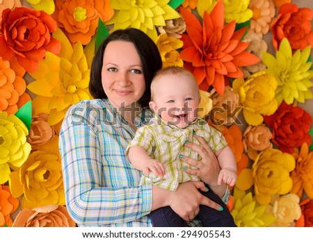 happy smiling young mommy hugging her laughing funny baby son on ornamental flowers background - stock photo