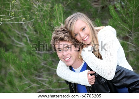 Happy smiling young natural teenagers in piggyback wearing winter  casual fashion - stock photo
