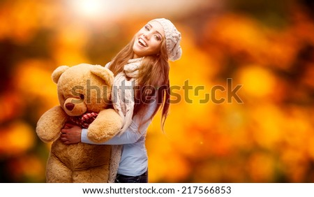 happy smiling young woman holding soft toy bear over autumn background - stock photo