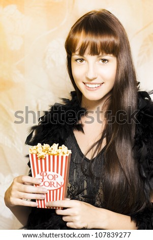 Happy smiling young woman in a feather boa holds an iconic traditional red and white striped box of delicious hot buttered popcorn during the intermission at showtime - stock photo
