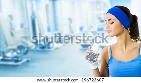 Happy smiling young woman in sportswear drinking water, at fitness club or center, with copyspace  - stock photo