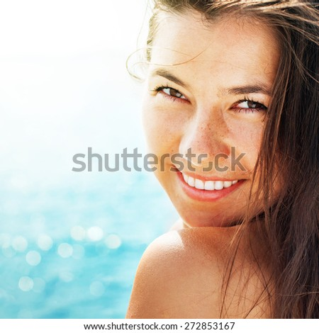 Happy smiling young woman on the background of sea in summer sunny day - stock photo