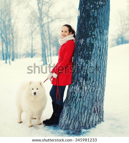Happy smiling young woman owner with white Samoyed dog walking in winter park - stock photo