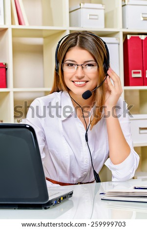 Happy smiling young woman surrort phone operator at her workplace in the office. Headset. Customer service. - stock photo