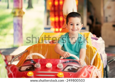 Happy smilling boy driving car toy at an amusement park. Toned photo. - stock photo