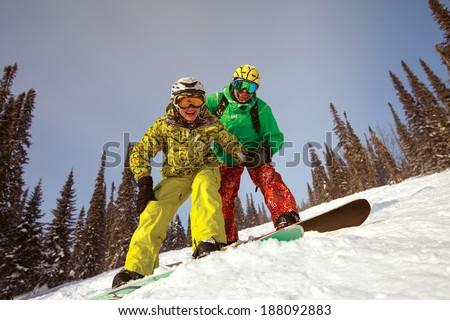Happy snowboarding  couple in winter mountains - stock photo