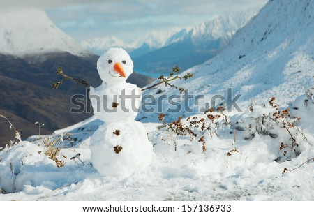 Happy snowman in mountains.  - stock photo