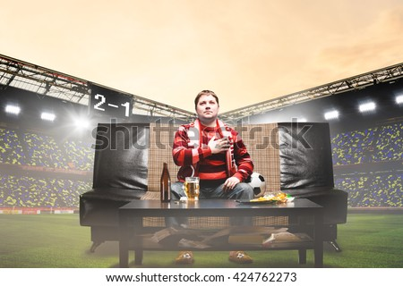 happy soccer or football fan with hand on heart on sofa at stadium - stock photo