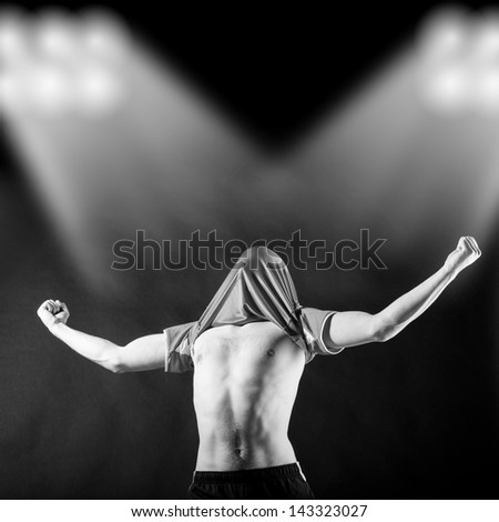 happy soccer player is celebrating in stadium light beams with jersey on head - stock photo