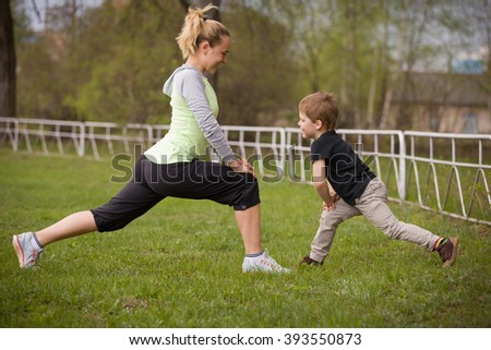 Happy son and mother are doing exercises in the summer park. on the stadium, outdoor. Sport activities with children. Healthy lifestyle. Fitness exercises. Young mother and son are stretching together - stock photo