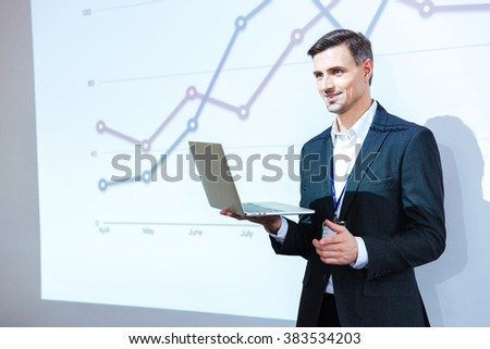 Happy speaker holding laptop and giving presentation in conference hall - stock photo